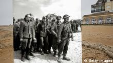 Fotomontage von Getty Images *** In this composite image a comparison has been made of Bernieres sur Mer, France. D-Day took place on June 6, 1944. *** COLOR 2014*** Image # 493783651. BERNIERES SUR MER, FRANCE - MAY 8: A view of Juno Beach on May 8, 2014 in Bernieres sur Mer, France. The Allied invasion to liberate mainland Europe from Nazi occupation during World War II took place on June 6, 1944. Operation Overlord, known as D-Day, was the largest sea borne invasion in military history. (Photo by Peter Macdiarmid/Getty Images) ***ARCHVE 1944*** Image # 461919359. Operation Overlord: A large number of German prisoners are gathered on the beach of Bernières-sur-Mer. June 1944. They are guarded by British soldiers from the 2nd Army on Juno Beach (Bernières sector). Bernières-sur-Mer, Normandy, France. (Photo by Galerie Bilderwelt/Getty Images)