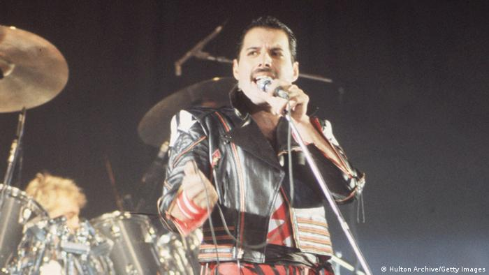 Freddie Mercury in leather sings onstage with a drummer behind him (Foto: Getty)