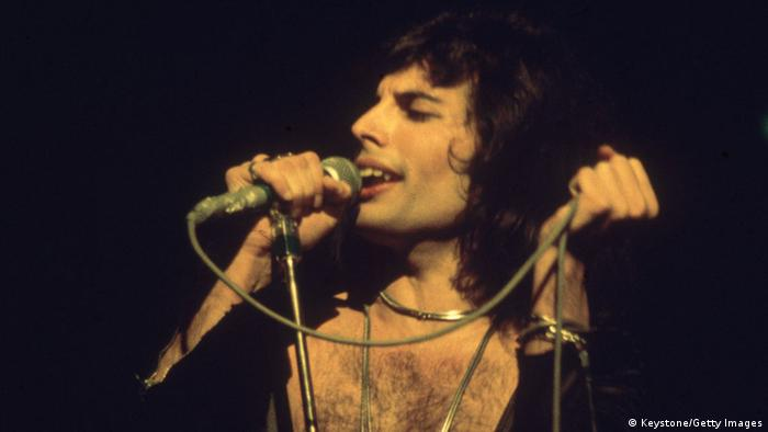 Freddie Mecury sings into a microphone under yellow lighting (Foto: