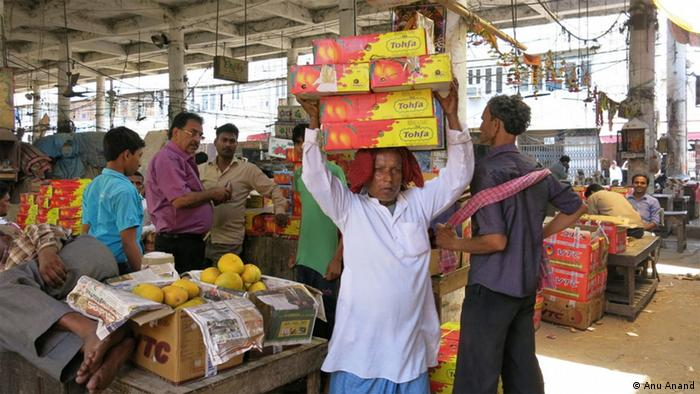 Man carrying boxes of mangos atop his head