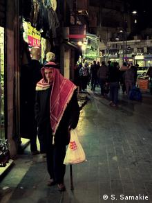 A man in a red kefiyeh strolls past a shop at night in Amman
