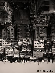 A black-and-white image of urban tower blocks turned upside-down