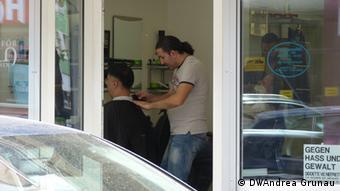 Der Frisör Hasan Yildirim schneidet einem Kunden die Haare (Foto: DW/A. Grunau)