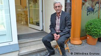 Metin Ilbay sitzt auf einem Hocker vor seinem Geschäft (Foto: DW/A. Grunau)
