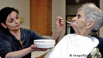 Njegovateljica hrani staricu