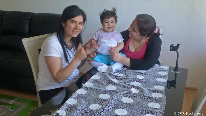 Evin Amir (l.) sitting at a table with her sister Nissrin (r.) and her baby daughter (Photo: Fabian Fischerkeller/ DW)