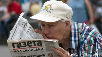 A woman reading a newspaper on Independence Square in Kyiv. (Photo: Vitaliy Belousov/RIA Novosti)