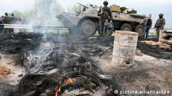 A Ukrainian tank and a soldier at a burned-out separatist barricade in Slavyansk, 02.05.2014. (Photo (c) dpa - Bildfunk)