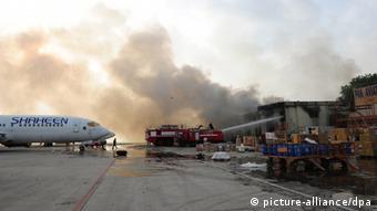 Пожарные тушат здание терминала, атакованного боевиками