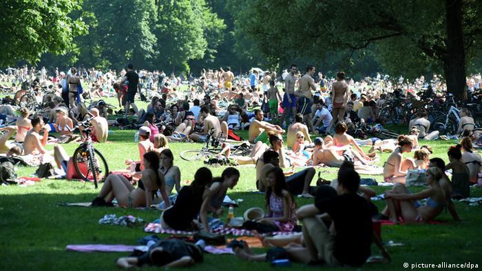 Menschen in einerm Stadtpark im Sommer (Foto: Felix Hörhager/dpa).