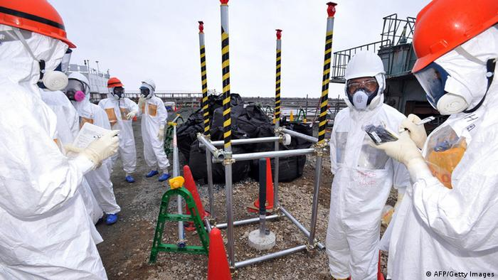 Local government officials and nuclear experts inspecting a monitoring well where high levels of radioactive materials were detected at Tokyo Electric Power's (TEPCO) Fukushima Dai-ichi nuclear plant in Okuma, Fukushima prefecture.