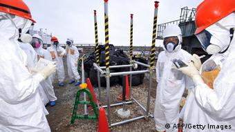 Local government officials and nuclear experts inspecting a monitoring well where high levels of radioactive materials were detected at Tokyo Electric Power's (TEPCO) Fukushima Dai-ichi nuclear plant in Okuma, Fukushima prefecture (Photo: JAPAN POOL/AFP/Getty Images)
