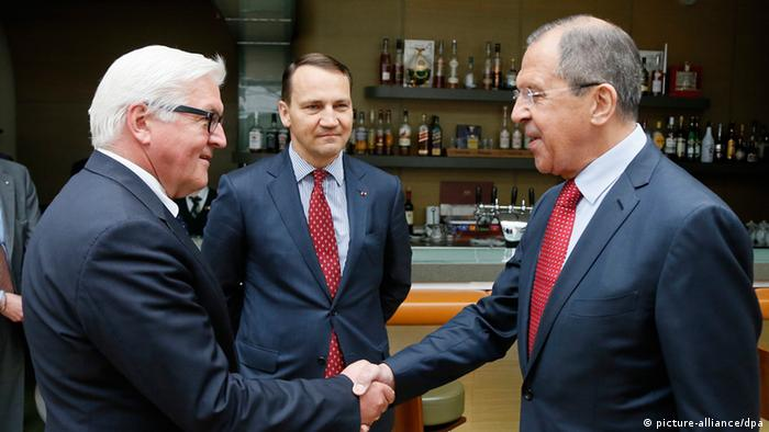Steinmeier, left, shakes the land of Lavrov, right as Sikorski looks on during a meeting in St. Petersburg, Russia
