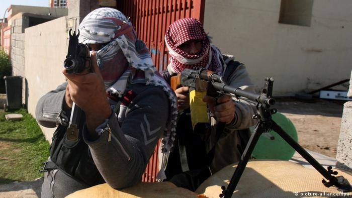 Man wearing head scarves and aiming automatic weapons near the camera