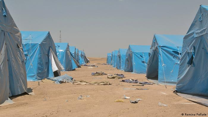 Two rows of blue tents in a desert Photo: Romina Peñate