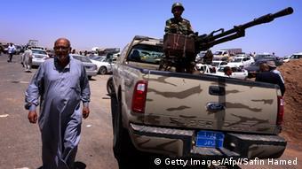 People walking alongside a military truck.