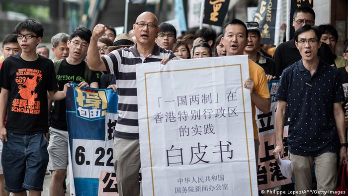 Demonstrators shout slogans holding a large reproduction of Beijing's White Paper as they march toward Beijing's representative office in Hong Kong on June 11, 2014.