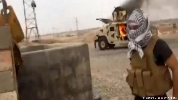 Offensive der ISIS Kämpfer am 12.06.2014. Ein Dschihadist steht vor einem brennenden Auto. Foto: Iraqi Revolution/AP Video