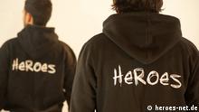 Junge Männer tragen Hemde mit dem Heroes Logo