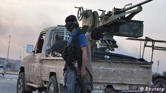 Ein ISIS-Kämpfer steht neben einem Pickup auf dem ein Geschütz montiert ist (Foto: REUTERS/Stringer)
