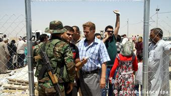 Soldiers check refugees at a checkpoint at Erbil