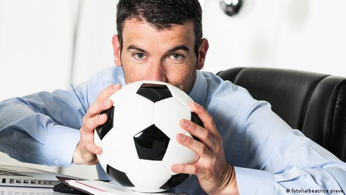 Мужчина с футбольным мячом в офисе