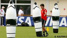 Germany's national soccer team coach Joachim Loew walks past dummies on the pitch during a training session of the German team in the village of Santo Andre north of Porto Seguro June 14, 2014. REUTERS/Arnd Wiegmann (BRAZIL - Tags: SOCCER SPORT WORLD CUP)
