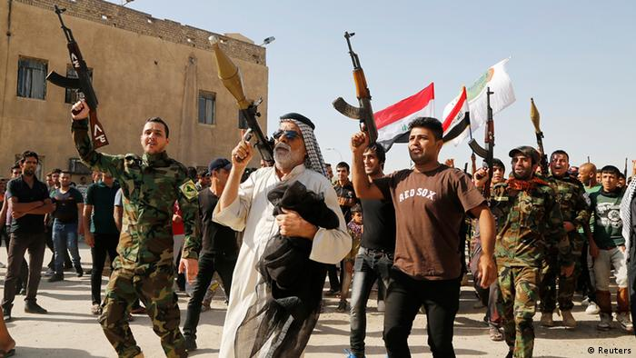 Volunteers who have joined the Iraqi Army to fight against predominantly Sunni militants carry weapons during a parade in the streets in Baghdad's Sadr city. REUTERS/Wissm al-Okili