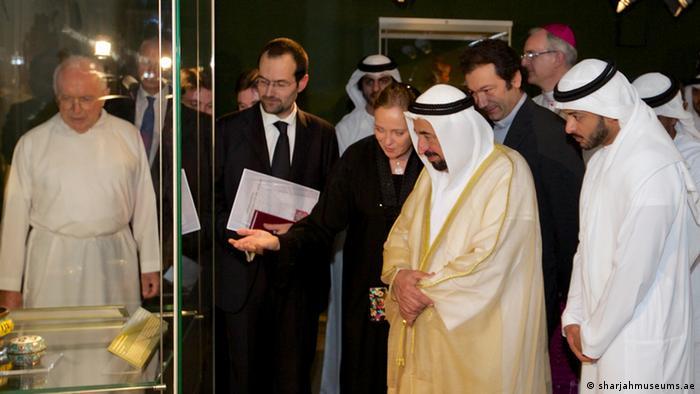 Ulrike Al-Khamis zeigt dem Herrscher Scharjahs, Scheich Sultan bin Mohammad al Qasimi (Mi.) und dem Direktor des Vatikanischen Ethnologischen Museums Fra Nicola Mapelli (li.) einige der Exponate
