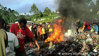 In this Wednesday, Feb. 6, 2013 photo, bystanders watch as a woman accused of witchcraft is burned alive in the Western Highlands provincial capital of Mount Hagen in Papua New Guinea.
