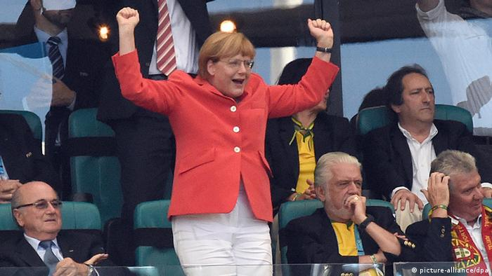 German Chancellor Angela Merkel celebrates after Mats Hummels scored a goal in the FIFA World Cup 2014 group G preliminary round match between Germany and Portugal .