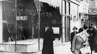 A pedestrian looks at the wreckage of a Jewish shop in Berlin in 1938