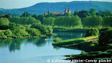 hinter einem langsam fließenden Fluss und versteckt von grünen Büschen und Bäumen erkennt man vor einem Hügel die Dächer einer Klosteranlage