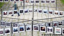 Ein Mann geht am 17.06.2014 beim 4. Lumix Festival für jungen Fotojournalismus an der Fachhochschule Hannover (Niedersachsen) vorbei an Fotografien. Auf dem ehemaligen Expo-Gelände sind vom 18. bis zum 22. Juni 60 Fotoreportagen aus aller Welt mit mehr als 1400 Bildern zu sehen. Foto: Julian Stratenschulte/dpa +++(c) dpa - Bildfunk+++