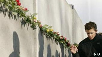 A visitor stands next to a segment of the Berlin wall, that has flowers stuck in it