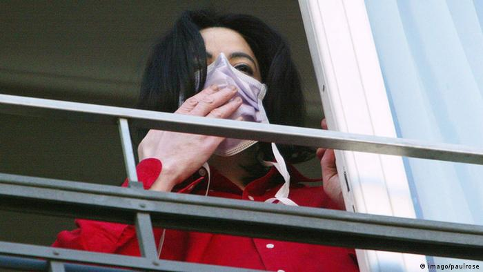 Michael Jackson looks out a window with a mouth mask on