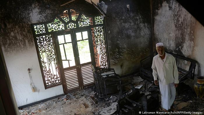 A Sri Lankan resident surveys the damage to a charred Muslim-owned home following clashes between Muslims and an extremist Buddhist group in the town of Alutgama on June 17, 2014.