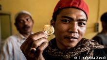 Portrait of Rizki holding a golden coin (Photo: Elisabetta Zavoli)