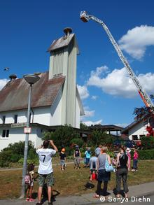 Böhringen villagers gathered watching fire truck ladder extended to church rooftop (Photo: Sonya Diehn)