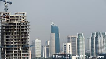 The construction of a new high rise building (L) rises over the skyline of Jakarta, Indonesia on February 5, 2013.