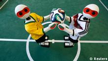 Humanoid robots dressed in the colours of Germany's and Brazil's national soccer team jerseys hold the official 2014 World Cup soccer ball during a photo opportunity at the Institute for Computer Science at the University of Bonn in Bonn June 18, 2014. The humanoid robots, which are developed by the University of Bonn's NimbRo team and company Igus GmbH, will compete at annual 2014 world robotic's championship RoboCup taking place in Brazil from July 21-24. REUTERS/Ina Fassbender (GERMANY - Tags: SOCIETY SPORT SOCCER SCIENCE TECHNOLOGY TPX IMAGES OF THE DAY)