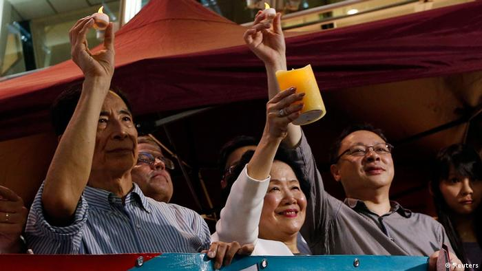 Former Hong Kong Chief Secretary Anson Chan (4th R), barrister and former lawmaker Martin Lee (3rd R), along with other supporters, sing at Hong Kong's financial Central district, to urge people to vote in an unofficial referendum, June 20, 2014. More than 200,000 people voted for full democracy in Hong Kong within the first few hours of an unofficial online referendum on Friday in a civil campaign that has sparked warnings from China's Communist Party leaders.