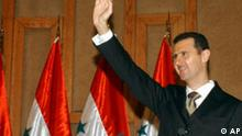 Syrian President Bashar Assad greets the audience at the Damascus University auditorium, where he delievered a political speech outlining all regional issues and the pressures facing Syria Thursday Nov. 10, 2005. Assad stressed that his country is innocent denying any involvement in Rafiq Hariri's murder, and pledged to cooperate with the investigation committee. (AP Photo /Bassem Tellawi).