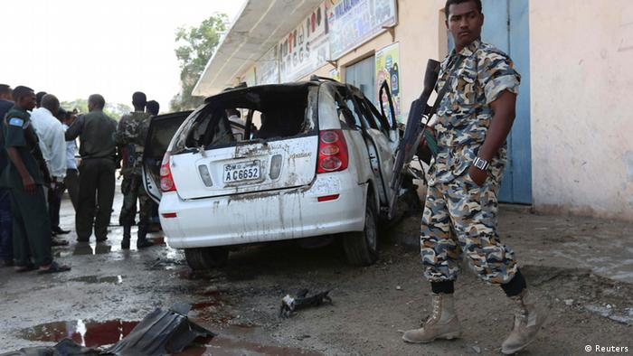 A Somali soldier stands in front of a bombed out car