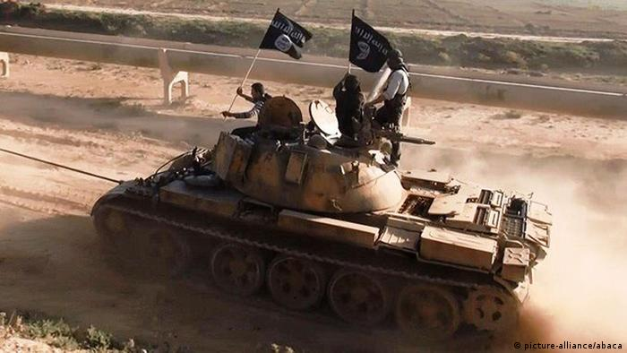 A tank flying the ISIS black-and-white flag in a desert setting
