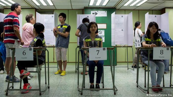 Assistants wait at polling station during a civil referendum held by Occupy Central in Hong Kong June 22, 2014. More than 200,000 people voted for full democracy in Hong Kong within the first few hours of an unofficial online referendum on Friday in a civil campaign that has sparked warnings from China's Communist Party leaders. REUTERS/Tyrone Siu