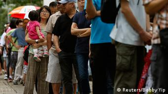 Voters line up outside a polling station during an unofficial referendum in Hong Kong June 22, 2014.
