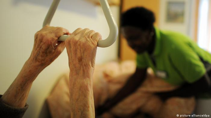 Hands holding on to hospital grab bar with carer in background