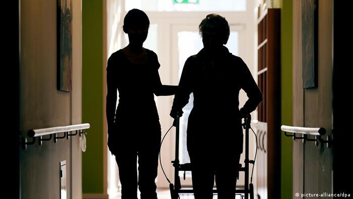 Ilustracija za njegovatelje: njegovateljica pomaže starijoj ženi s hodalicom, obje u sjeni