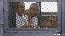 Al Jazeera journalists (L-R) Peter Greste, Mohammed Fahmy and Baher Mohamed stand behind bars at a court in Cairo in this June 1, 2014 file photograph. An Egyptian judge sentenced three Al Jazeera journalists on June 23, 2014 to seven years in jail after finding them guilty on charges including helping a terrorist organisation by publishing lies. The three include Australian Greste, Al Jazeera's Kenya-based correspondent, and Canadian-Egyptian national Fahmy, bureau chief of Al Jazeera English. A third defendant, Egyptian producer Mohamed, received an additional three-year jail sentence on a separate charge involving possession of weapons. REUTERS/Asmaa Waguih/Files (EGYPT - Tags: POLITICS MEDIA CRIME LAW TPX IMAGES OF THE DAY)